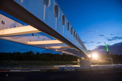 La passerelle, assemblée sur le côté de l'autoroute, a été poussée centimètre par centimètre au‐dessus de l'autoroute